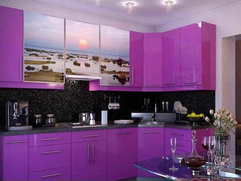 This small kitchen has small backsplash tiles that match with the grainy black backsplash. These black elements make the light purple hues of the cabinetry stand out. The middle floating cabinets are adorned with a sunset ocean scenery.