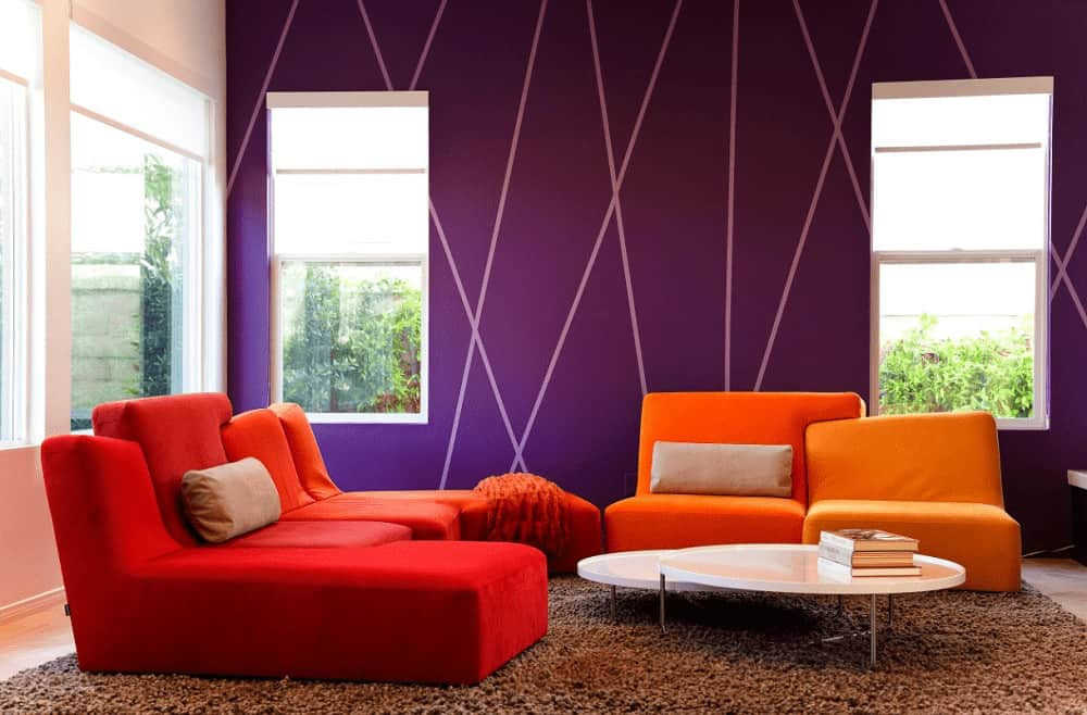The modern living room features a round modular coffee table and vibrant orange seats creating a striking contrast to the purple wall. It has a brown shaggy rug and glazed windows that allow natural light in.