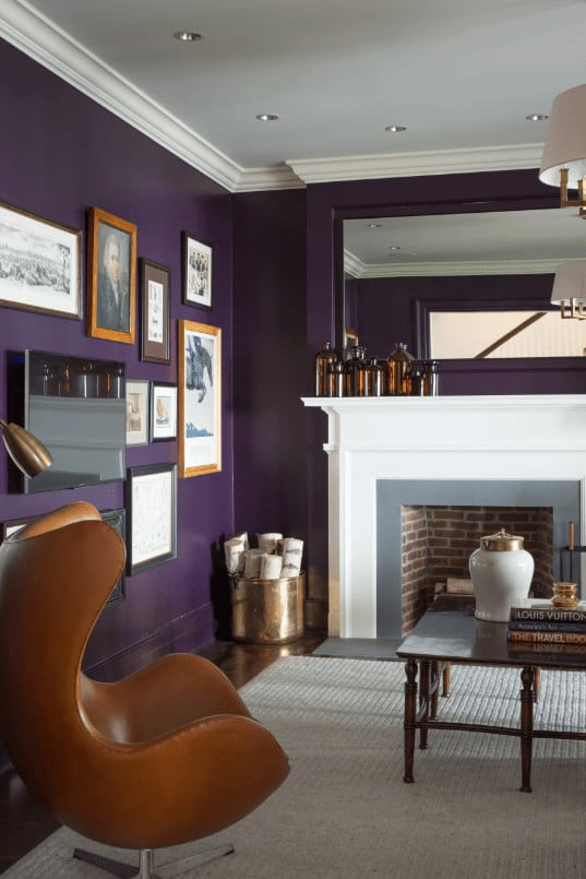 A modern amber chair faces the wooden coffee table across the brick fireplace framed in gray surround and white mantel. This room has a photo gallery wall and dark hardwood flooring topped by a gray area rug.