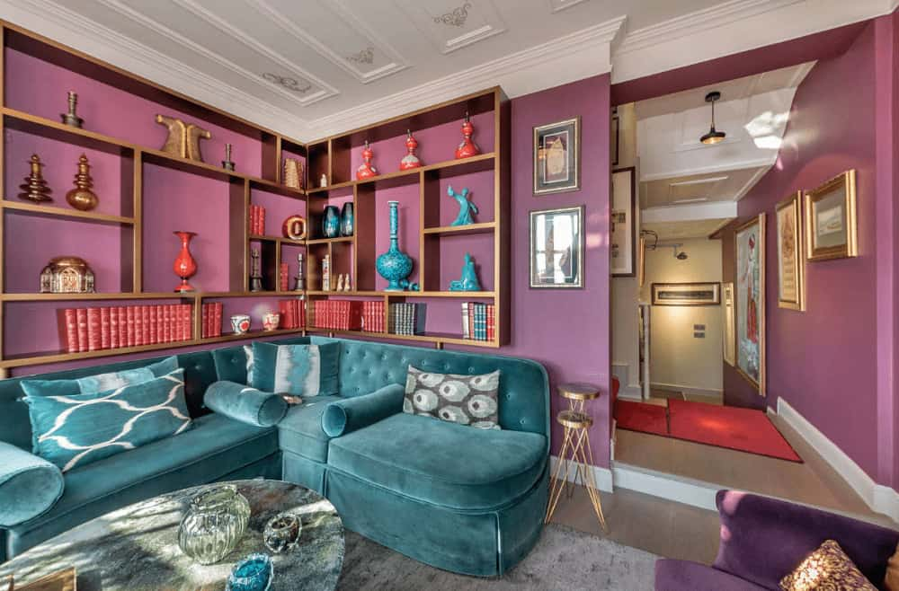 Eclectic living room boasts built-in shelving and a blue velvet sofa paired with a coffee table that's topped with glass bowls. It has a stylish ceiling and purple walls lined with white <a class=