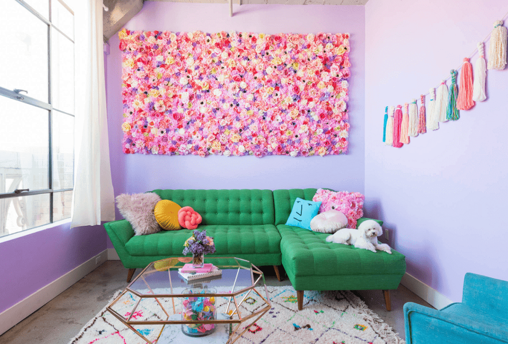 This living room is decorated with pastel tassel garland and lovely floral wall art that hung above the green tufted sofa paired with a geometric glass coffee table.