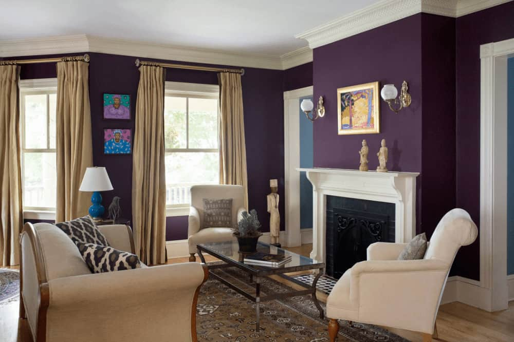 A lovely artwork hangs above the fireplace accompanied by beige seats and a metal coffee table over a brown area rug. It is illuminated by globe sconces mounted on the purple wall.