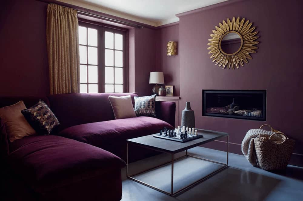 This living room is decorated with a sunburst mirror mounted above the modern fireplace. It is furnished with a metal coffee table and an L-shaped sofa that blends in with the wall.