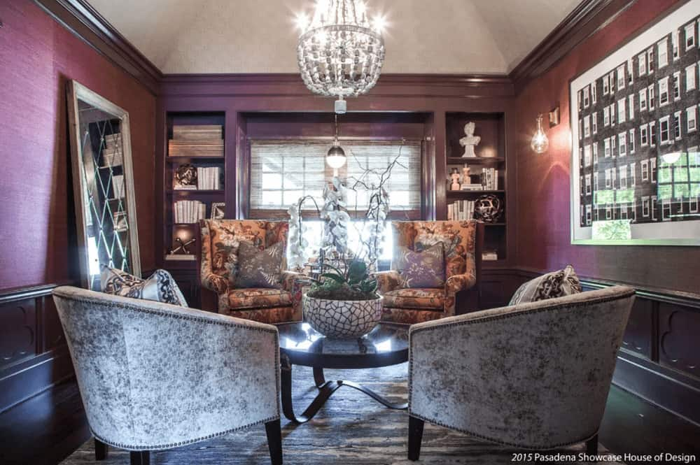 A gorgeous chandelier illuminates this living room featuring a large wall art and stylish full-length mirror that lays on the purple wall. It has gray and floral armchairs surrounding a black coffee table over a gray area rug.