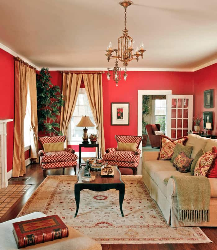 A skirted sofa faces the black coffee table in this living room with red patterned wingback chairs and a floral rug that lays on the rich hardwood flooring.