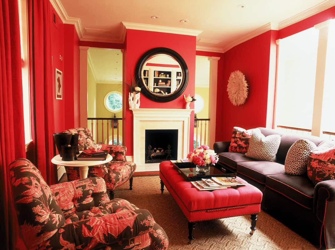 A white fireplace provides a sleek contrast to the red walls mounted with round mirror and furry decor. This room has cozy seats and a red tufted ottoman topped with a black tray and glass flower vase.