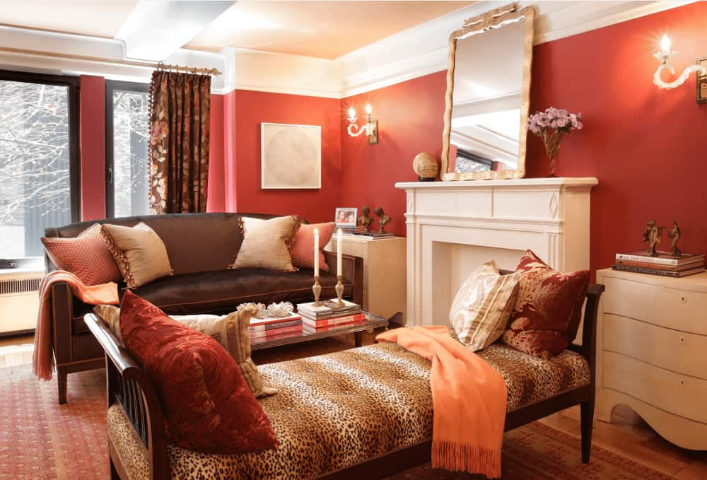 The fabulous living room offers a black leather sofa and leopard bench filled with fluffy pillows and peach throw blankets. It includes candle sconces and a white fireplace with a chrome framed mirror on top.