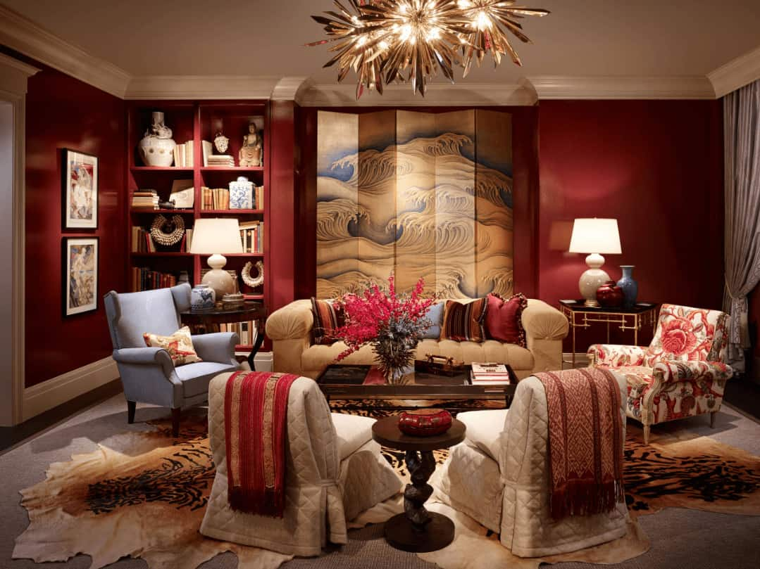 A wave painted screen sets a nice backdrop to the beige tufted sofa accompanied by mismatched chairs and tables. It is illuminated by stunning sunburst chandeliers and white table lamps.