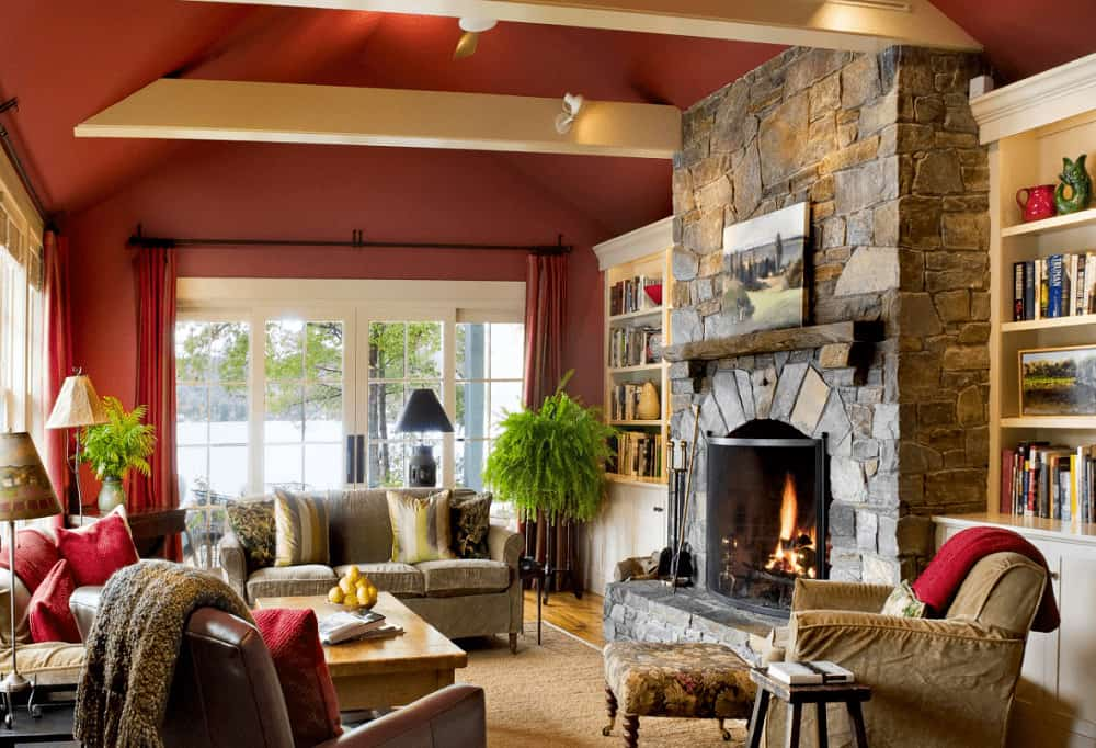 White built-in shelvings flank a stone fireplace in this rustic living room offering comfy seats and a wooden coffee table that sits on a jute area rug.