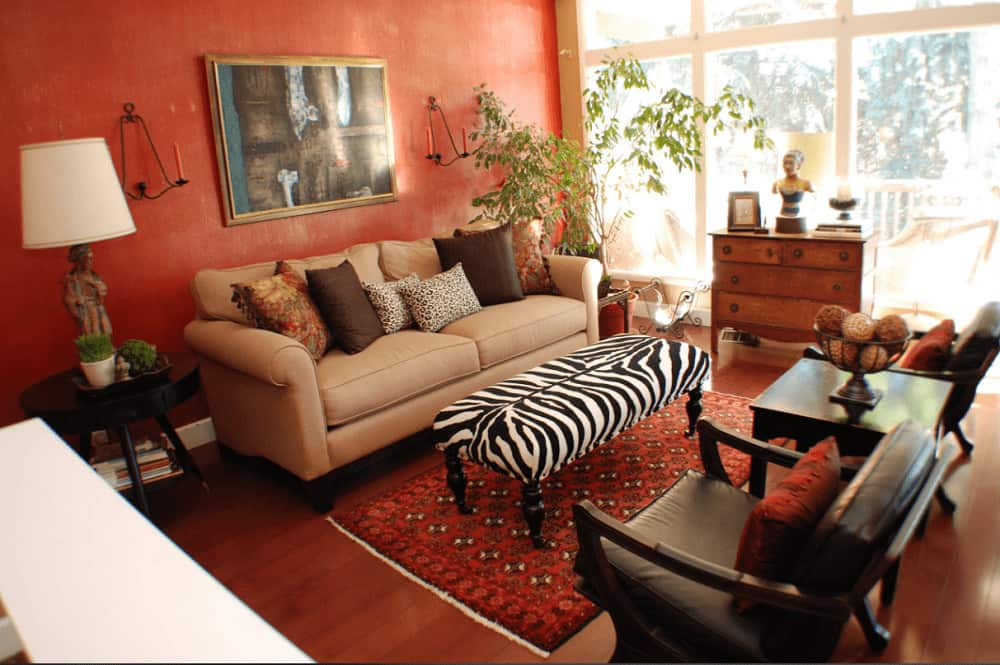 A zebra ottoman stands out in this red living room offering cozy seats and a wooden drawer that complements the smooth hardwood flooring topped by a red patterned rug.