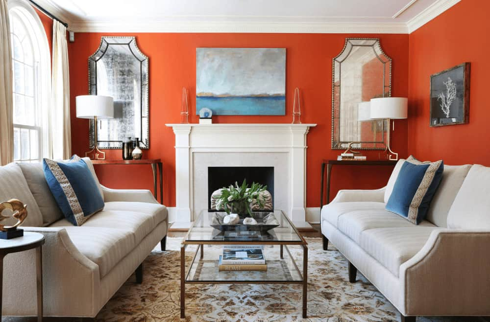 Traditional living room with a glass top coffee table and a white fireplace accented with an abstract painting. It includes a pair of gorgeous mirrors and facing sectionals that add perfect symmetry to the room.