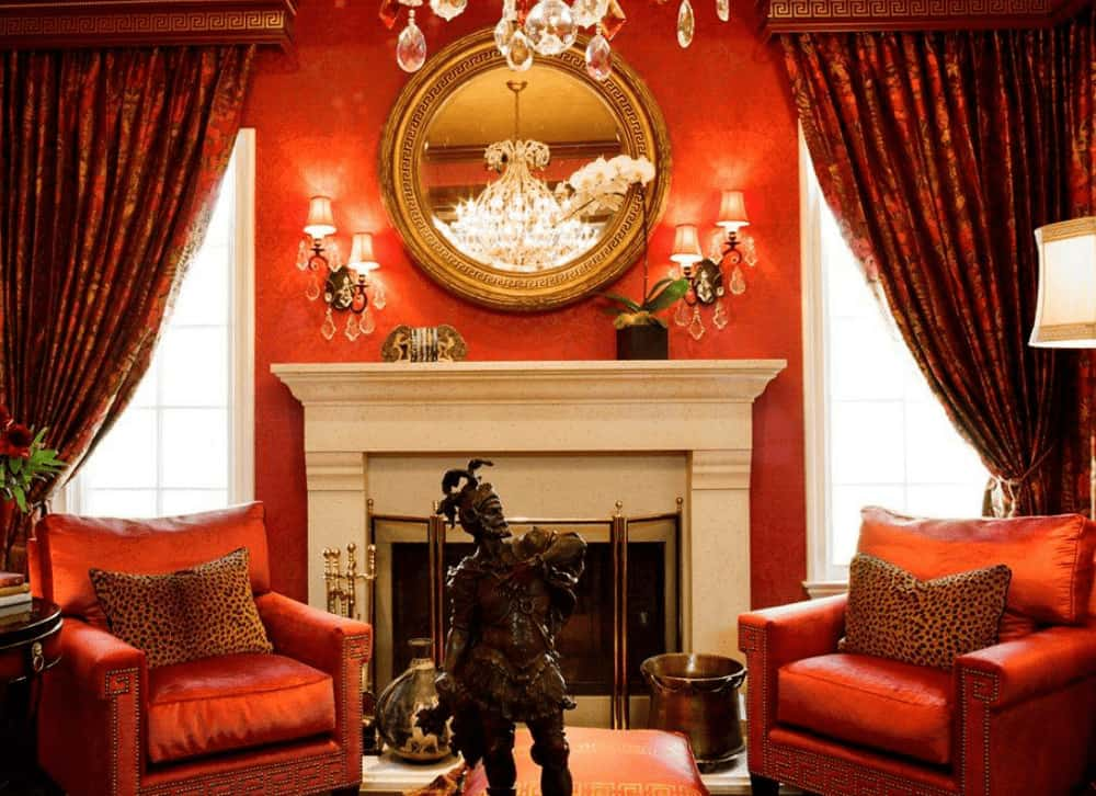 The luxury living room showcases red armchairs and a fireplace situated in between white framed windows that are dressed in classy draperies. It is decorated with antique sculpture and brass framed mirror lighted by crystal sconces.