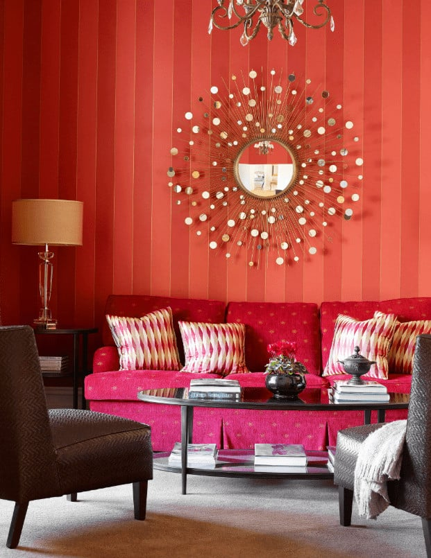 A sunburst mirror adds a gorgeous accent to the red striped wallpaper in this living room with skirted sectional and gray textured chairs surrounding the oval coffee table.