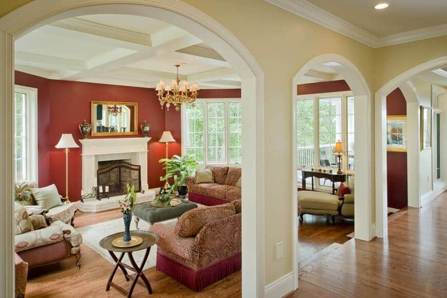 This living room is illuminated by traditional floor lamps and a brass chandelier that hung from the coffered ceiling. It has cozy seats and a white fireplace covered with an ornate wrought iron fence.