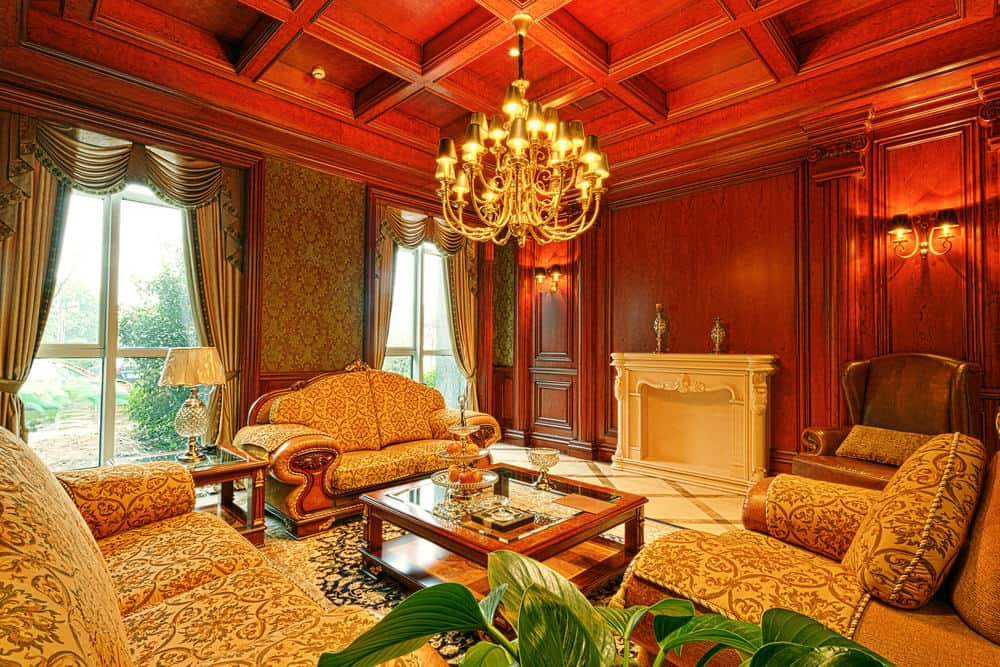 Red living room with coffered ceiling, chandelier, and valance curtains on floor-to-ceiling windows.