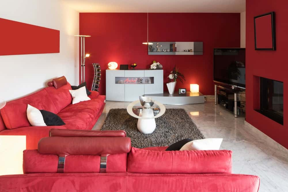 This living room features a stylish white coffee table surrounded by glass enclosed fireplace and red velvet sectionals. There's a flat screen TV in the corner and a shaggy area rug that lays on the marble tiled flooring.
