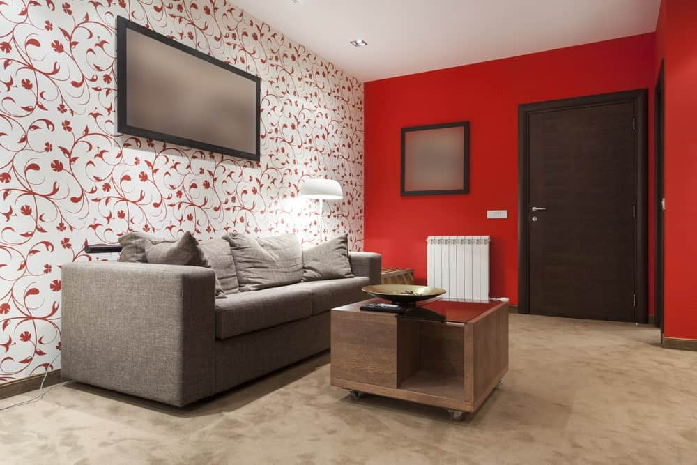 Clad in red floral wallpaper, this living room features a comfy gray sofa filled with matching fluffy pillows along with a wooden coffee table that's fitted with rollers.