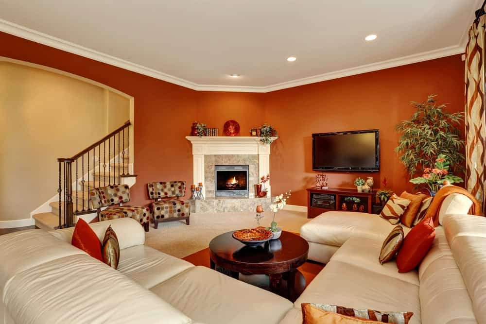 Red living room with a fireplace and wall mount TV that hung above the wooden stand. It includes dotted chairs and a white sectional paired with a round coffee table.