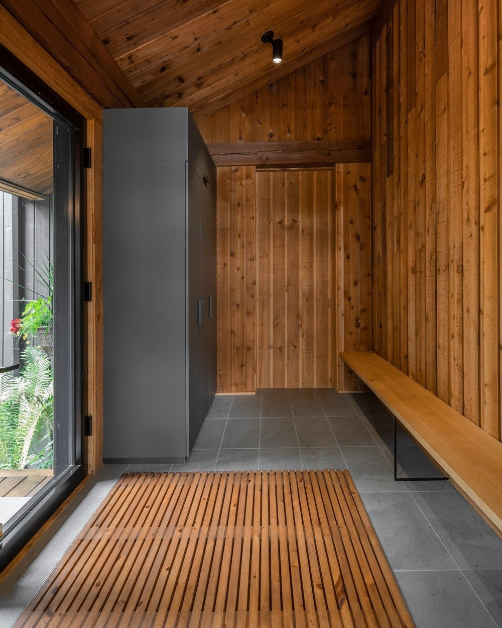 A rustic foyer with a wooden shed ceiling and hardwood walls, along with gray tiles flooring and a long bench seating on the side.