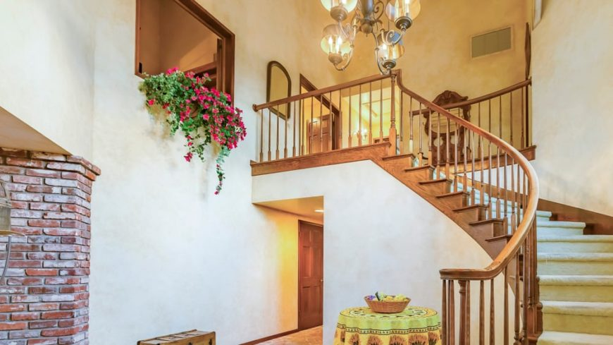 This is a large rustic foyer with a wooden staircase, a tall ceiling with rustic chandelier and flowering vines on the indoor balcony above.