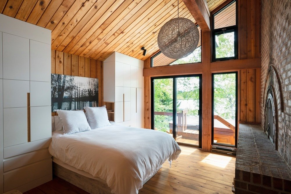 Rustic primary bedroom featuring a wooden shed ceiling along with hardwood flooring. There's a large brick fireplace set in front of the bed.