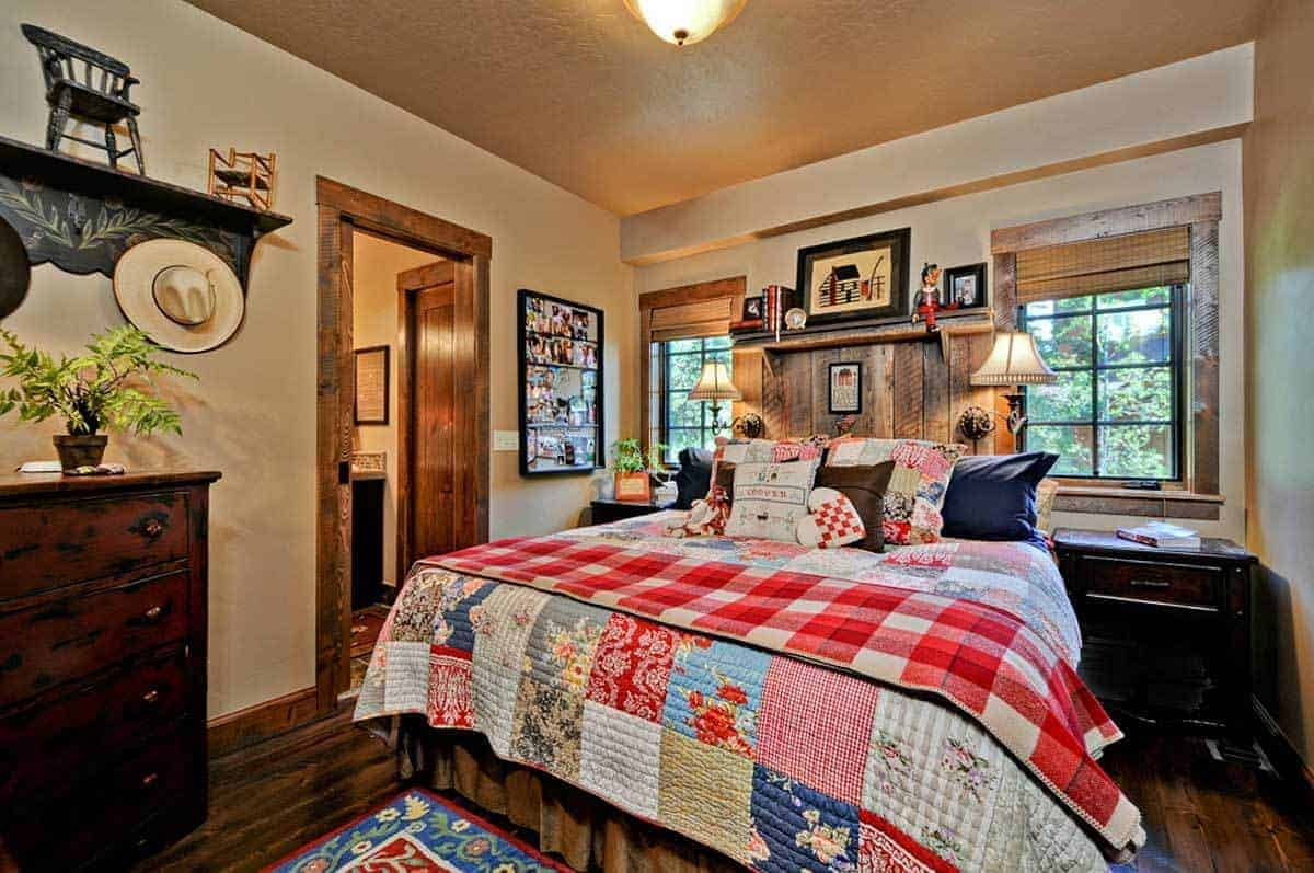 This is a charming and homey Rustic-style primary bedroom that embraces and comforts with its colorful traditional bed flanked with bedside drawers and brilliant windows with frames that blend with the wooden plank headboard accented with wall-mounted lamps.