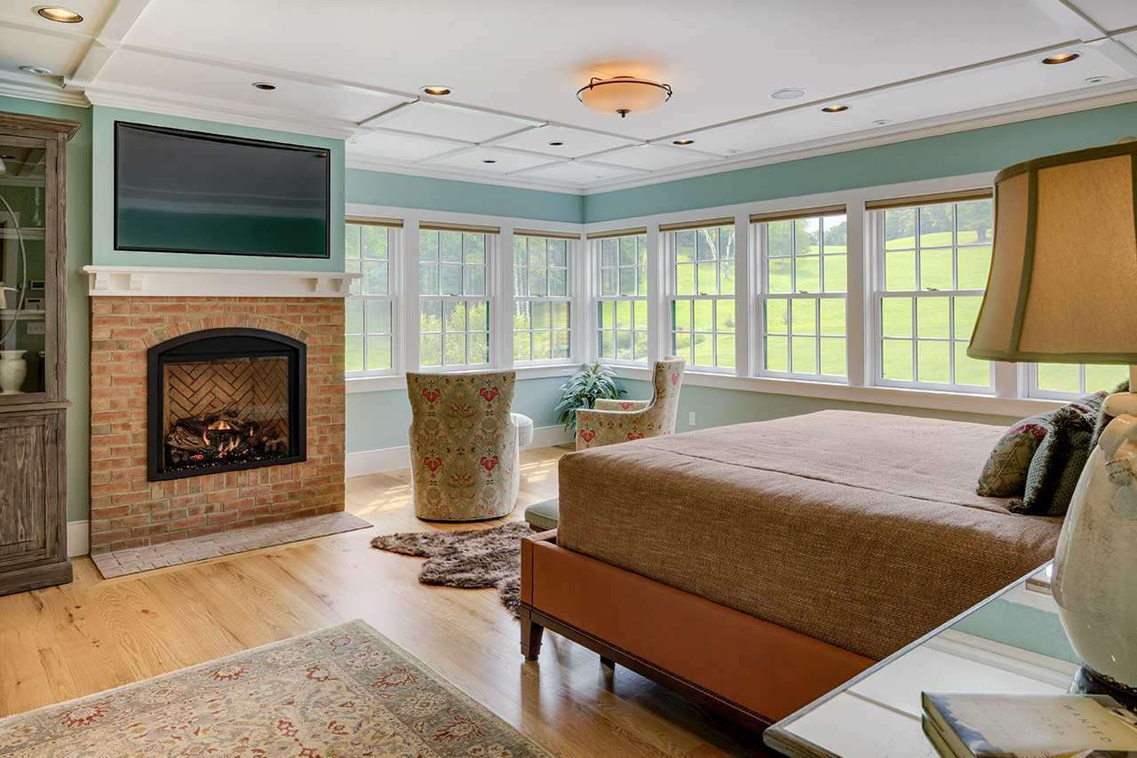 The bright row of white windows bring in an abundance of natural lighting to the white ceiling and light hardwood flooring that complements the red brick inlay of the fireplace by the foot of the traditional bed beside the sitting area that has a couple of floral cushioned armchairs.