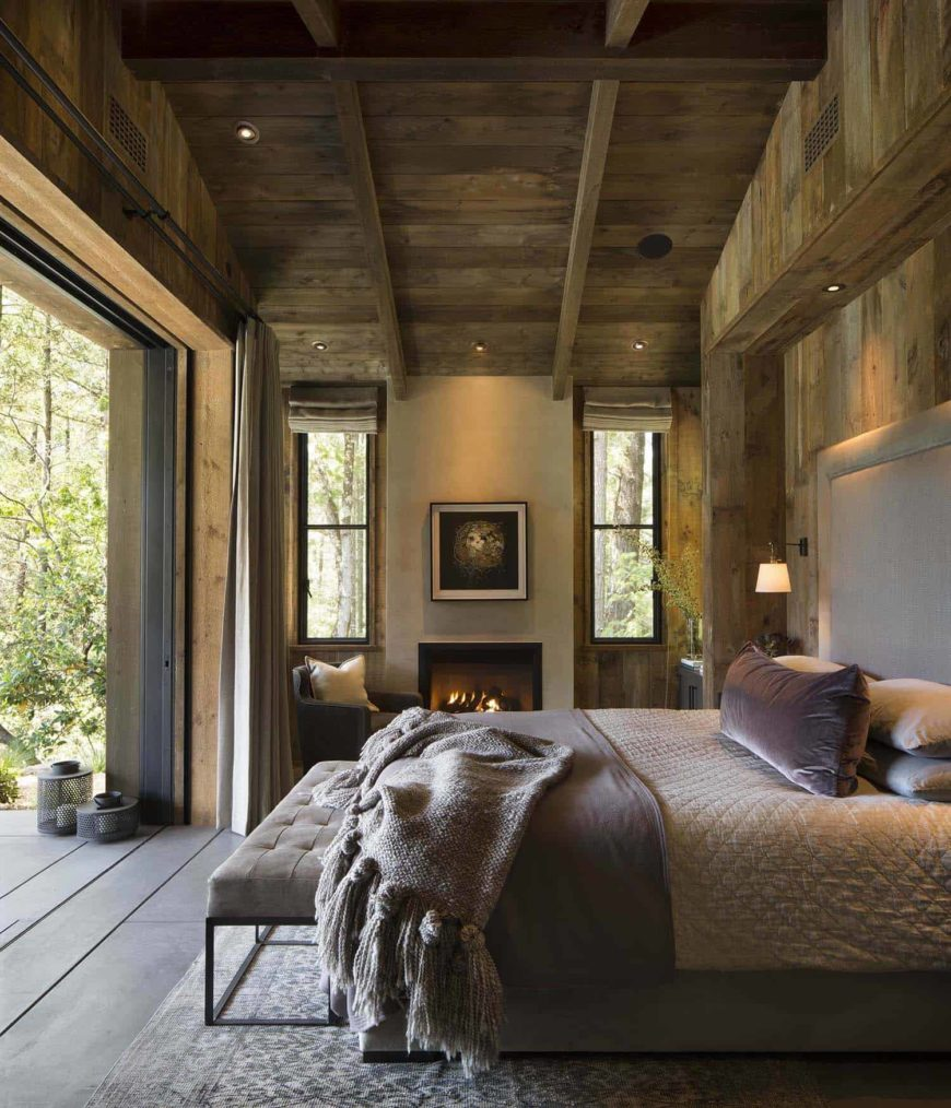 This relaxing Rustic-style primary bedroom maximizes the beautiful outdoor scenery with its wall by the foot of the bed that opens up. Adjacent to this is a fireplace flanked by windows by the bed. These are all topped with a high wooden cathedral ceiling with exposed wooden beams.