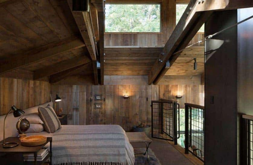 The simple gray bed with gray sheets and gray headboard complements the wooden walls and ceiling that has exposed wooden beams. These beams and wooden ceiling are brightened by the brilliant transom windows.