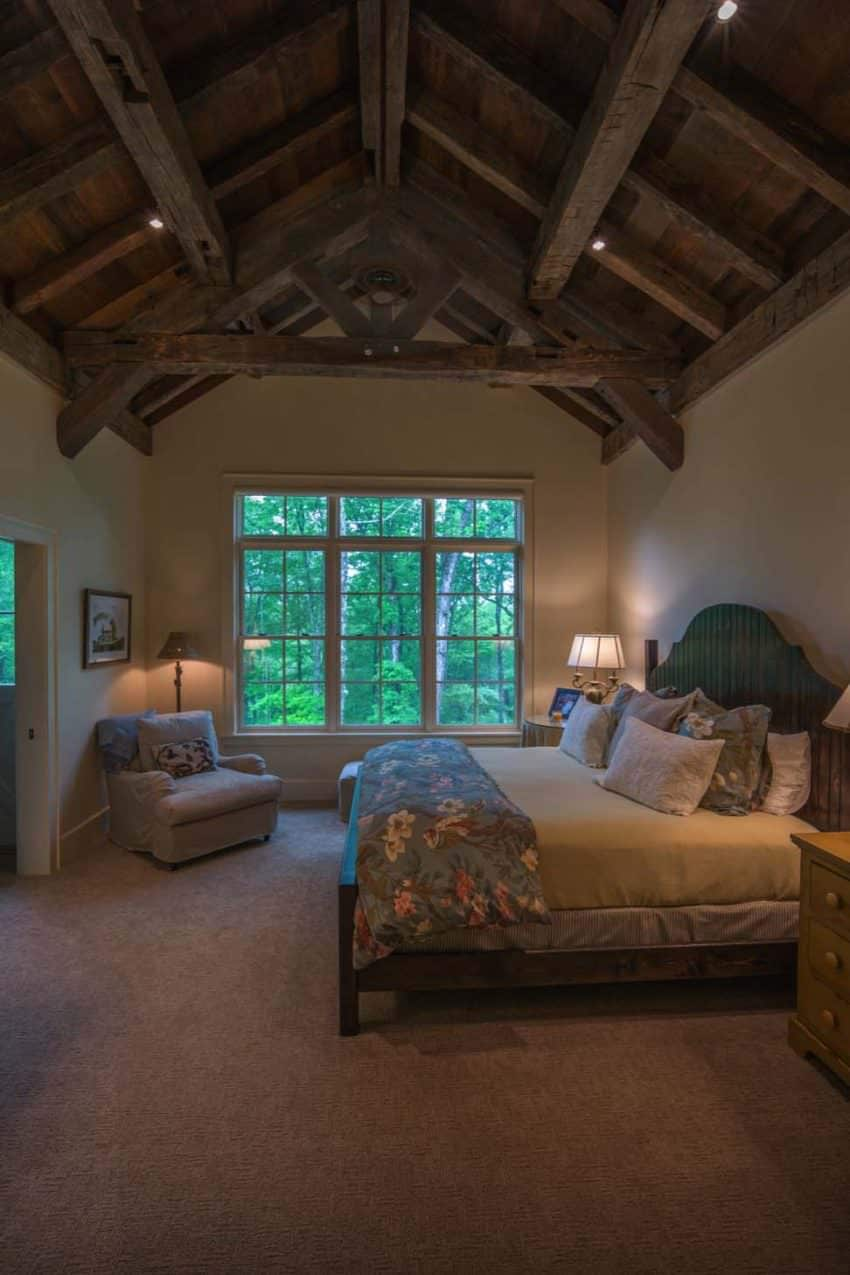 The wooden cathedral ceiling and its exposed wooden beams complement the beige walls of this Rustic-style primary bedroom. This is mirrored by the wooden frame of the large bed and its beige sheets that are illuminated by the bedside table lamps.