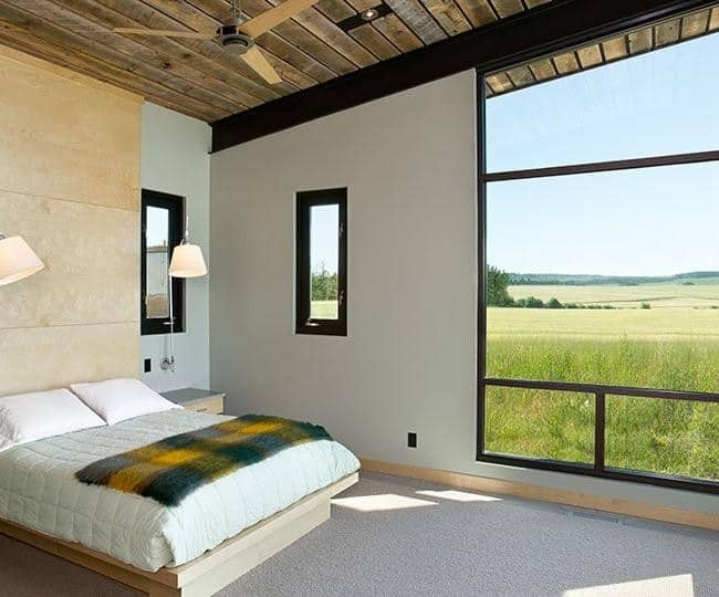 This Rustic-style bedroom has simple white walls and wooden ceiling that complements the wooden platform bed on the simple light gray carpeted flooring. All these simple elements bring the focus to the brilliant scenery outside the large windows.