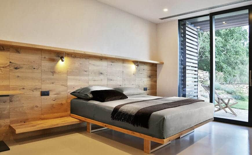 The wooden platform bed supports a thick cushion with gray sheets and gray pillows. This makes it stand out against the wooden wall behind it that has a single shelf beneath it extending to the sides that serve as bedside tables and another shelf above that supports spot lights.
