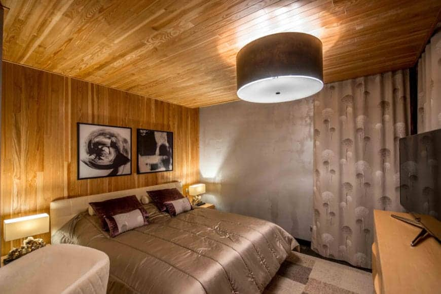 The gray comforter of the beige bed matches with the gray patterned area rug and the gray patterned curtain by the gray wall. These are all balanced by the wooden wall, entertainment cabinet and the ceiling that has a black semi-flush mount lighting.