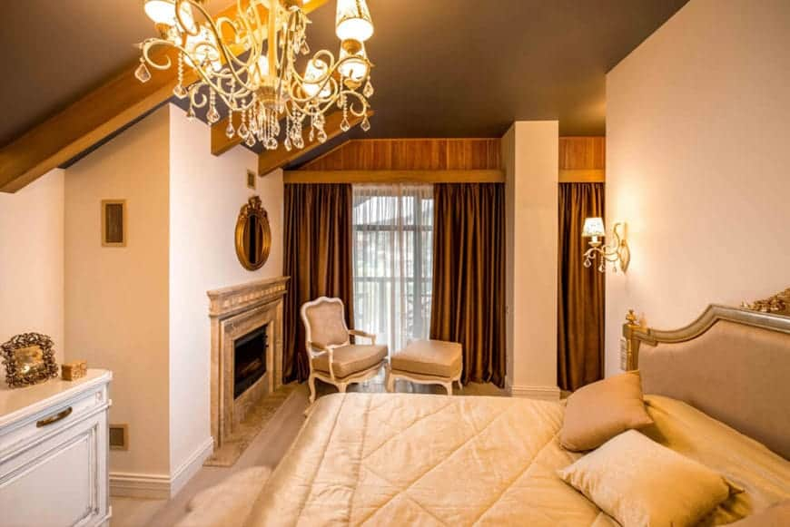 This elegant Rustic-style bedroom has a black ceiling that is augmented by the exposed wooden beams as well as the warm yellow lights of the majestic chandelier hanging over the beige sheets of the bed. There is a nice sitting area by the fireplace on the side by the curtained window.