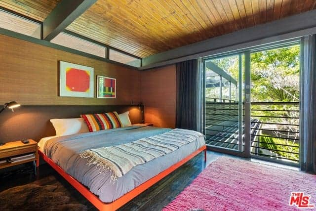 The traditional bed has an orange hue to its frame that makes it stand out against the dark hardwood flooring topped with a woven pink area rug that is brightened by the natural lights of the glass sliding doors that leads to a small balcony.