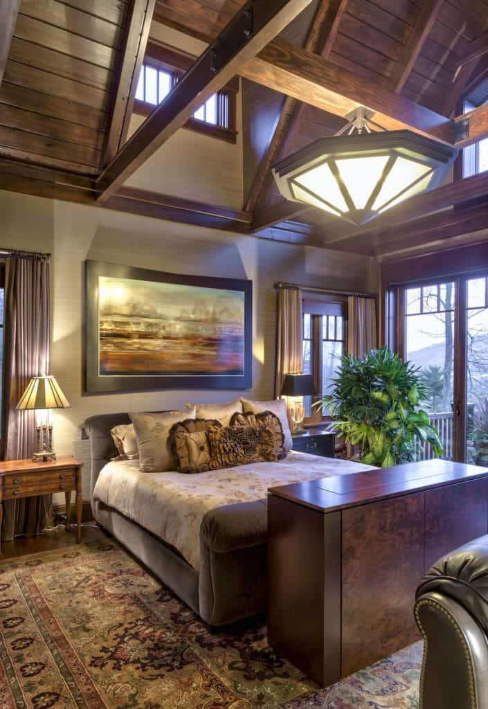 The high wooden ceiling has a cathedral design with exposed wooden beams and brilliant transom windows that illuminate the ceiling. It sets a charming view for those who are lying down on the gray cushioned sleigh bed that is accented with a colorful painting above it.