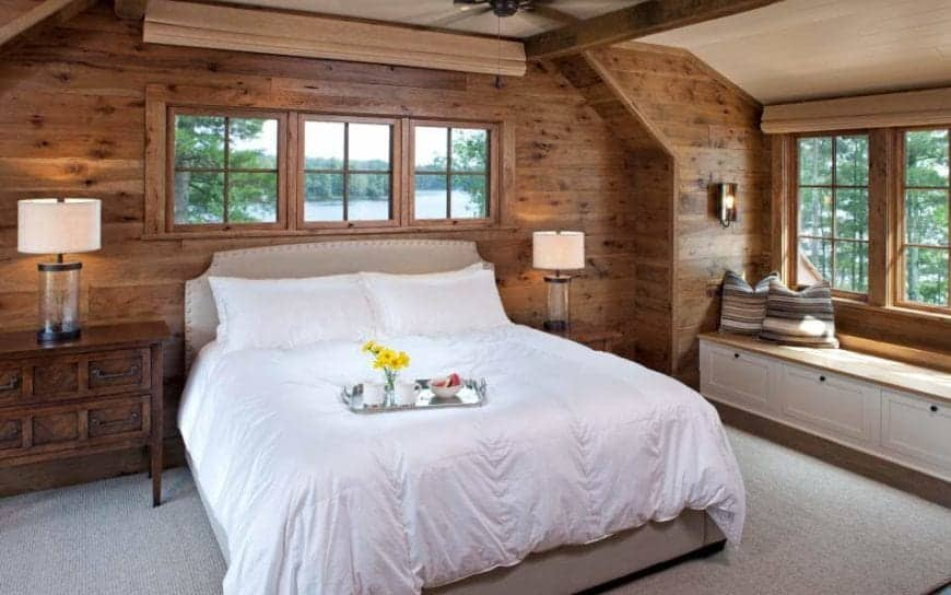 This is a charming Rustic-style bedroom with a light gray bed that has white sheets standing out against the gray carpeted flooring and the wooden walls. By the bed is a lovely sitting area with a built-in wooden bench by the window.