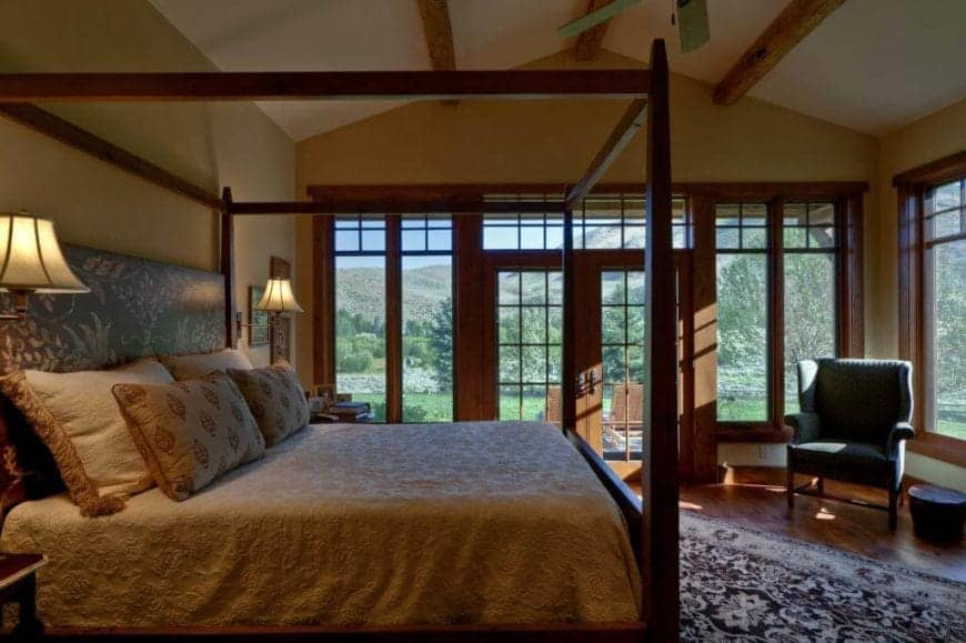 The lovely dark wooden four-poster bed has light brown sheets and pillows that are enhanced by the warm yellow lights of the wall-mounted lamps flanking the bed. This setup is given a lovely background of glass windows and doors that showcase the lush landscape outside.