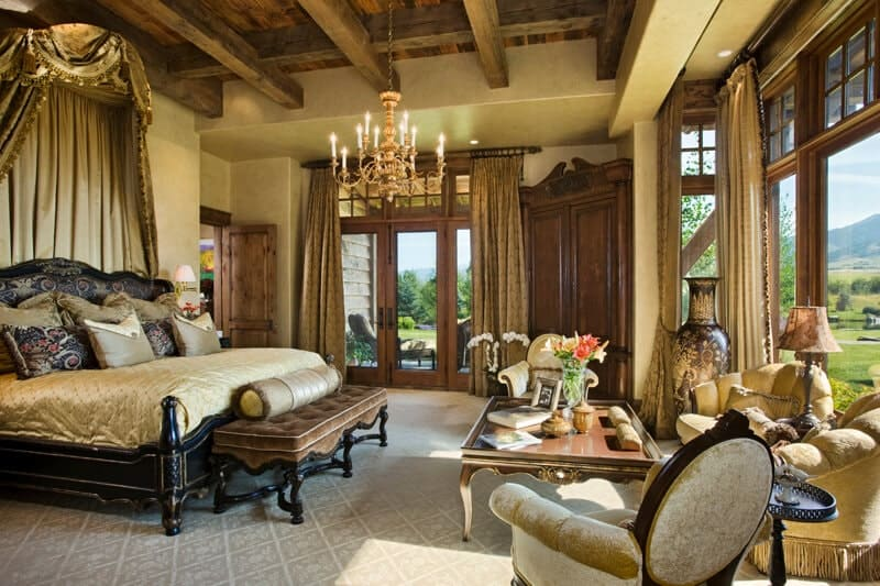 The wooden ceiling above the black elegant bed has exposed wooden beams that support the majestic golden chandelier that hangs in between the bed and the sitting area by the window that has beige couches and a wooden coffee table.