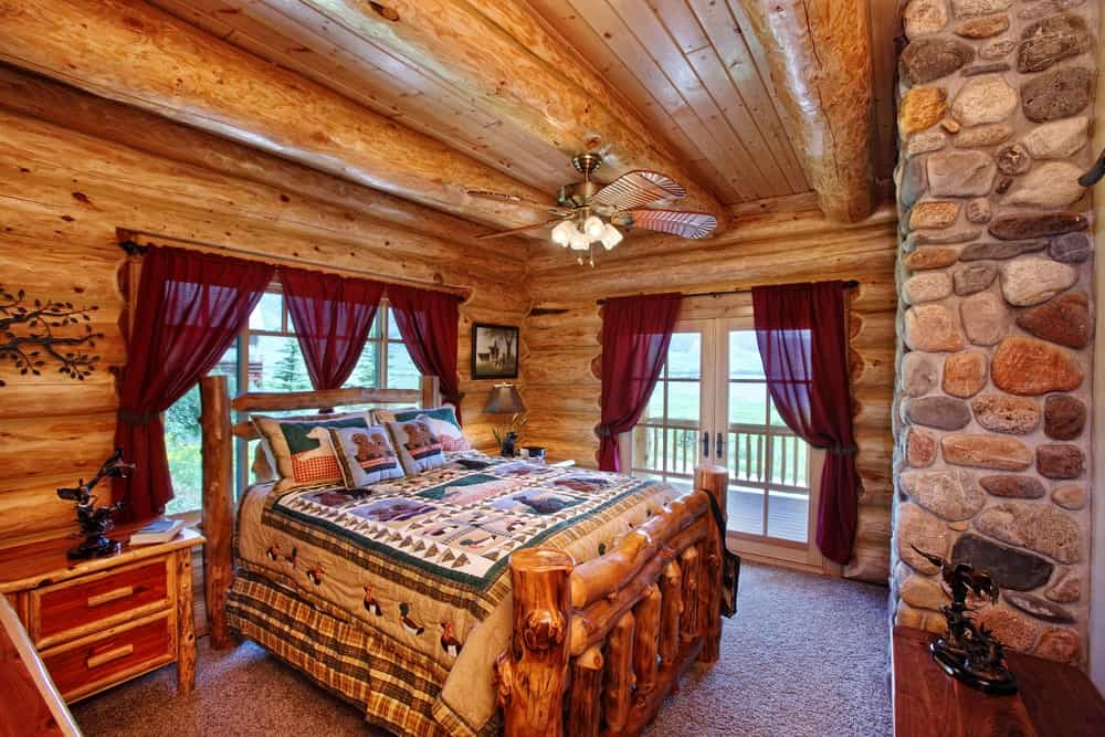 The charming wooden bed is made of rough tree trunks with branch stumps. This matches with the log cabin walls and wooden ceiling with exposed thick wooden log beams that support a decorative ceiling fan that has lighting.
