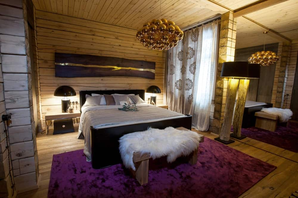 The purple velvet area rug over the hardwood flooring stands out in this room that has wooden walls and ceiling. From the ceiling hangs a decorative chandelier that looks like a bunch of golden spheres. This hangs over the black traditional bed that matches the black modern table lamps.