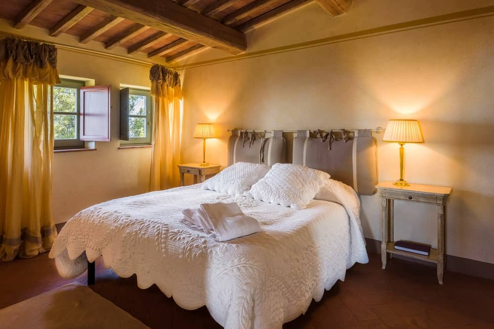 The white sheets of this traditional bed stands out against the dark terracotta bricks of the floor. This goes well with the beige walls that are augmented by the warm yellow lights of the table lamps on wooden bedside tables that match the wooden ceiling with exposed beams.