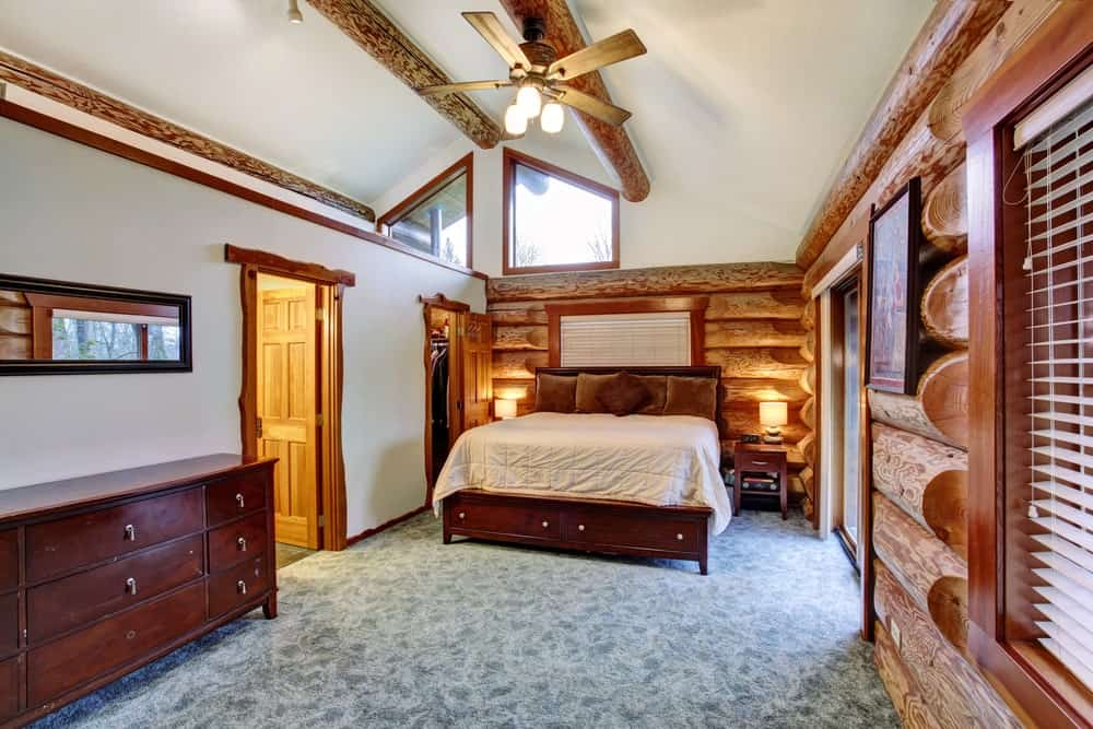 The white cathedral ceiling is brightened by the transom windows and adorned with exposed wooden logs that matches with the log beams of the walls that are illuminated with warm yellow light from the bedside lamps of the wooden traditional bed.