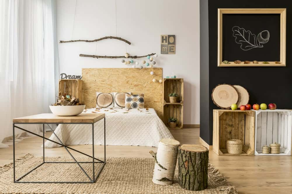 This is a bright rustic bedroom mostly due to its white walls that are brightened by the natural lights of the curtained window. The white elements are balanced by the wooden adornments as well as the hardwood flooring.