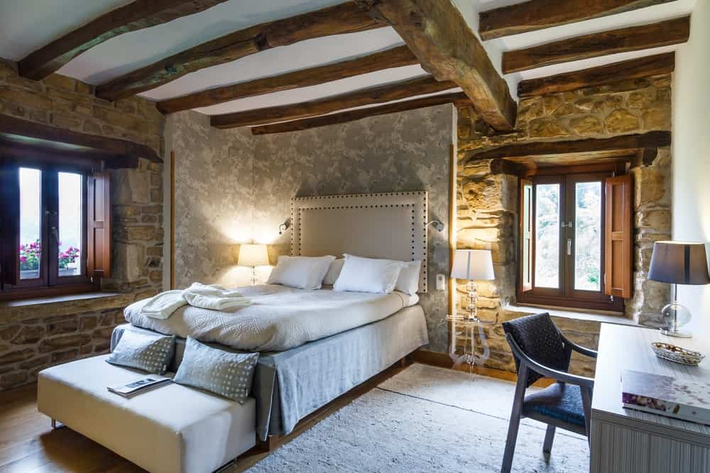 The white ceiling is adorned with beautiful irregular textured wooden beams that set a unique aesthetic to this Rustic-style bedroom that has rough stone walls and hardwood flooring that gives emphasis on the beige platform bed.