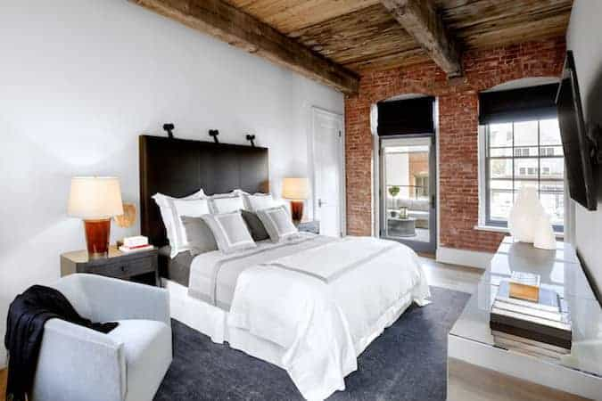 This primary bedroom has a Rustic-style old wooden ceiling with massive wooden beams. This pairs well with the red brick wall that houses the glass door and large glass window that bring in natural lights to the dark wooden headboard of the white bed.