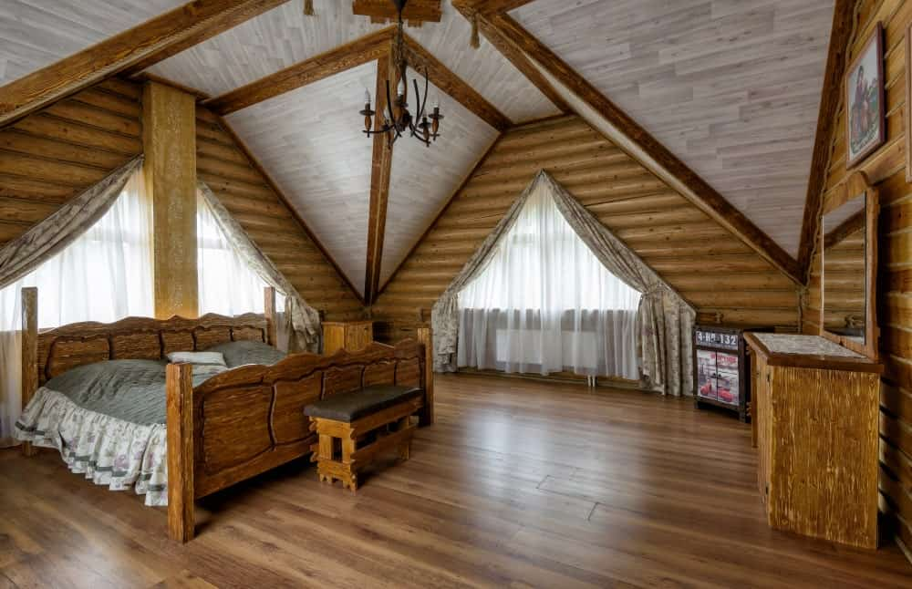 The walls of this Rustic-style bedroom is made of log beams and they are dominated by the low arches of the ceiling and the triangular windows that bring in natural lights to the large wooden bed that matches with the hardwood flooring.