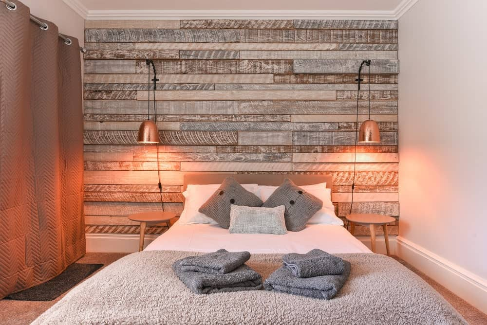 This simple Rustic-style bedroom has a platform bed with white cushions and pillows flanked by small wooden stools for bedside tables. The head of the bed is against a wall that is made of planks arranged in a textured finish and adorned with warm yellow lights.