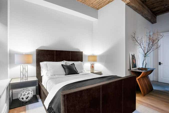 The dark brown leather upholstery of the of the mission-type bed makes it stand out against the white walls that are further brightened by the brilliant modern table lamps on the bedside tables flanking the bed. These are all balanced by the wooden ceiling and the hardwood flooring.