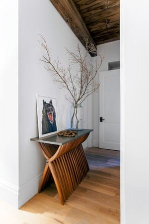 This is a small and simple Rustic-style foyer with a white wooden main door. Upon entry of this, you are welcomed with a wooden ceiling and hardwood flooring complemented by a decorative console table with a glass top adorned with decors.